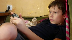 Boy playing game joystick online video game console Stock Footage