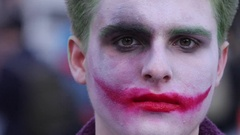 A man in joker clown halloween make up face portrait Stock Footage