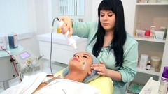 Receiving electric darsonval facial massage procedure. Stock Footage
