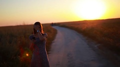 Portrait of a beautiful girl with a smartphone in the evening at sunset Stock Footage