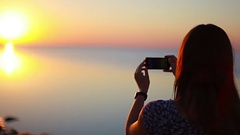 A girl takes a photo of a bright sun at sunset Stock Footage