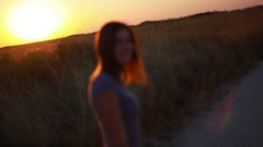 A walk of the beautiful light brown girl along the bright red sunset sky Stock Footage