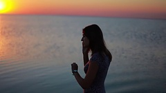 Girl listening to voicemail on the phone, lake in the evening Stock Footage