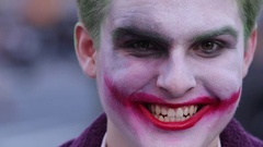 A man in joker clown halloween make up face portrait laughing Stock Footage
