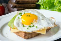 Breakfast fried egg, avocado and cheese on bread Stock Photos