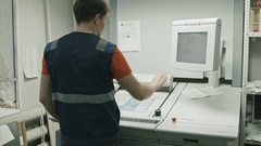 Poligraphy industry - worker checks colours and use touch screen monitor for Stock Footage