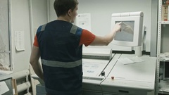 Poligraphy industry - worker use touch screen monitor for printed process, rear Stock Footage
