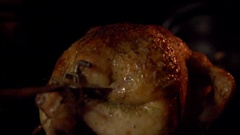 A bird roasted on a spit in an oven in close-up. Stock Footage