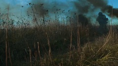 Ukrainian soldier aims and walk on the field through the smoke Stock Footage