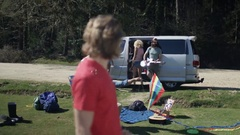 4K Portrait of smiling hipster guy with friends at music festival campsite Stock Footage