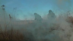 Ukrainian soldier aims, stand and walk on the field through the smoke Stock Footage