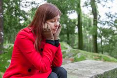 Young woman feeling depressed sitting on a stone table and bench on a forest Stock Photos