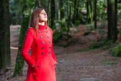 Woman enjoying the warmth of the winter sunlight on a forest wearing a red ov Stock Photos