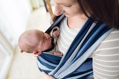 Close up, beautiful mother carrying her son in sling Stock Photos