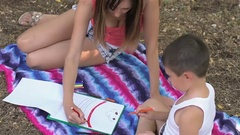 Mother and son paint a rainbow on a sheet of paper in the Park Stock Footage