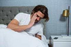 Man waking up from sleep in bedroom Stock Photos