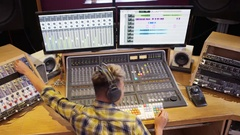 4K Young sound engineer working at the mixing desk in recording studio Stock Footage