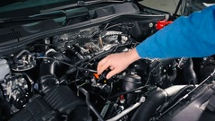 The wizard checks wires under the hood of a car. Stock Footage
