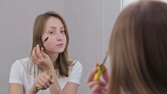 Beautiful young woman putting mascara in front of mirror Stock Footage