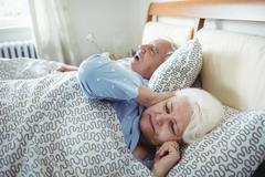 Man snoring and woman covering her ears while sleeping on bed Kuvituskuvat