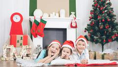 Happy kids laughing and smiling on background of christmas tree and fireplace Kuvituskuvat