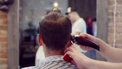 The man in the Barber shop . Barber masterfully makes the cut for her client Stock Footage