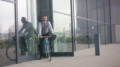 4K Portrait, cheerful businessman leaving office building on a bicycle Stock Footage