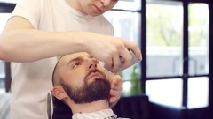 Hairdresser for men red beard and mustache to his client, a young man Stock Footage