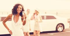 Portrait of women holding champagne next to limousine Kuvituskuvat