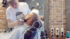 Male businessman makes the cut head and beard in a Barber shop for men Stock Footage