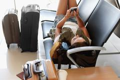 Female tourist using smartphone in waiting hall Stock Photos