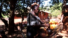 Africa woman preparing Caju juice for wine fermentation in village - Guinea Stock Footage