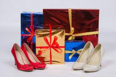 Red and white female shoes with high heels, standing near boxes with gifts Stock Photos