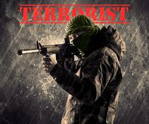 Dangerous masked and armed man with terrorist sign on grungy background Stock Photos