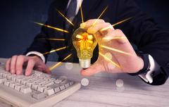 Business person holding an electric light bulb Stock Photos