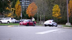 Old lady accidentally driving car on median island with police car on scene Stock Footage