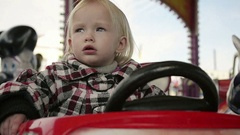 Close Up of a Little Girl Riding on a Carousel in Amusement Park Stock Footage