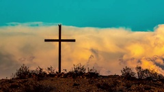 Time Lapse of cross on a desert hill at sunset with birds Stock Footage