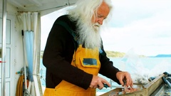 Fisherman filleting fish Stock Footage