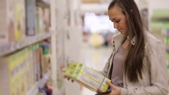 Young woman is choosing a corn flakes in the supermarket. Stock Footage