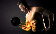 Bodybuilder athlete lifting weight with fire explode arm concept Stock Photos