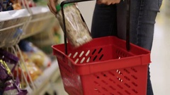 Woman puts goods in red shopping basket at the supermarket Stock Footage