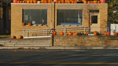 Tilt up-Morning after Halloween post office decorated with pumpkins Stock Footage