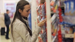 Young woman is choosing baby food in jar the shopping centre. Stock Footage