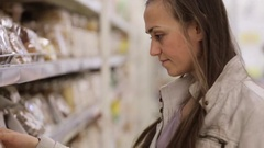 Young woman is choosing a zephyr in the sweet section of the shopping centre. Stock Footage