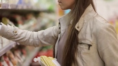 Woman selecting corn in grocery store produce department. Stock Footage