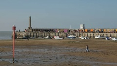 Couple walking at low tide across the beach at the Harbour Arm Stock Footage