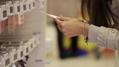 Young caucasian woman selects a barrette in the shopping centre. Stock Footage