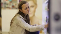 Young caucasian woman choosing deodorant in beauty section of shoping centre. Stock Footage