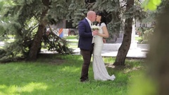 Happy groom holds in arms and kisses his bride Stock Footage